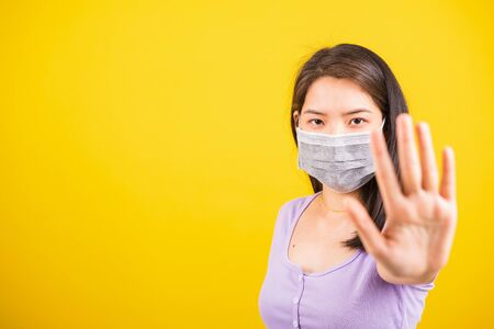 Asian young teen woman wearing face mask protective against coronavirus or COVID-19 virus or filter dust, air pollution her raise palm hand to no or stop sign, isolated yellow background 스톡 콘텐츠