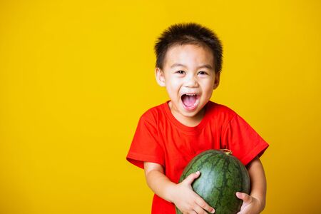 Happy portrait Asian child or kid cute little boy attractive smile wearing red t-shirt playing holds full watermelon that has not been cut, studio shot isolated on yellow background