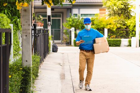 Asian young delivery man courier hold parcel post boxes he protective face mask service and walk looking for customer home location, under curfew pandemic coronavirus COVID-19 Zdjęcie Seryjne