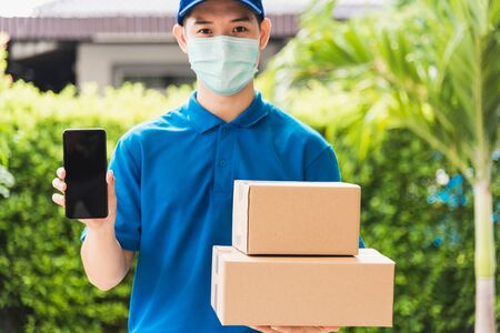 Asian delivery express courier young man giving boxes to customer he wears protective face mask at front home and show mobile phone blank screen, under curfew quarantine pandemic coronavirus COVID-19