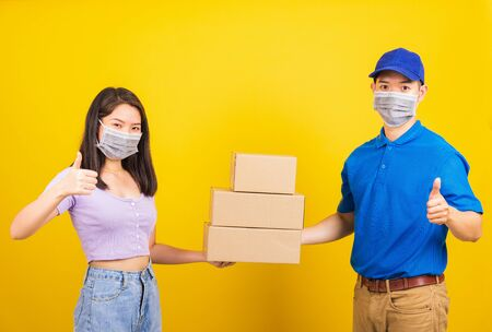 Asian beautiful woman and handsome man wearing protection face mask against coronavirus, accepting delivery boxes, studio shot isolated on yellow background, COVID-19 or corona virus concept Zdjęcie Seryjne