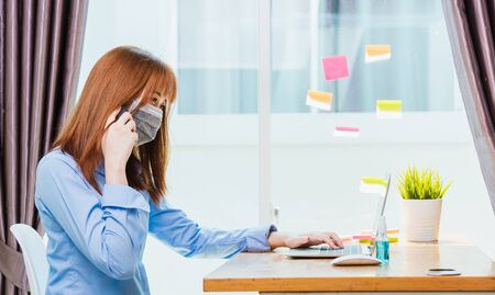 Work from home concept, Asian young business woman wearing face mask protective quarantines disease pandemic coronavirus or COVID-19 her working on desk with laptop computer at home office