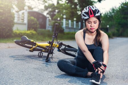 Beautiful young female woman pain injured accident sitting after bicycle falling with copy space Stok Fotoğraf