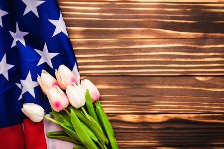 Happy Memorial Day Remember previously but now seldom called Decoration Day, American USA flag and a Tulip flower on wooden background and copy space, a federal holiday in the United States