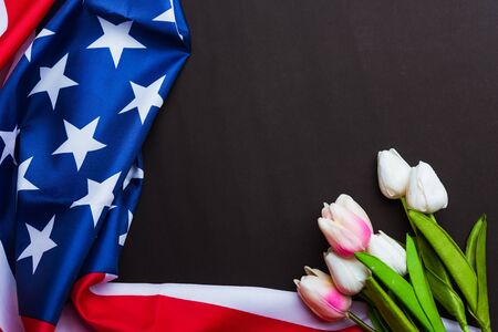 Happy Memorial Day Remember previously but now seldom called Decoration Day, American flag and a Tulip flower on a black background and copy space, a federal holiday in the United States