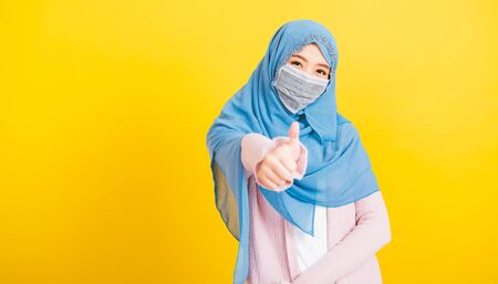 Asian Muslim Arab, Portrait of happy beautiful young woman religious wear veil hijab smiling she show finger thumb up for a good sign, studio shot isolated yellow background with copy space