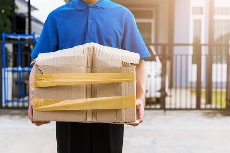 Asian young delivery man in blue uniform he emotional falling courier hold damaged cardboard box is broken at door front home, Accident bad transport shipment or poor quality delivery service concept