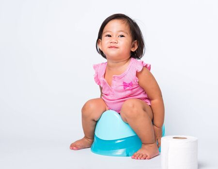 Asian little cute baby child girl education training to sitting on blue chamber pot or potty with toilet paper rolls, studio shot isolated on white background, wc toilet concept Stock Photo