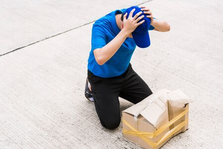 Asian young delivery man in blue uniform he emotional falling courier hold damaged cardboard box is broken at door front home, Accident bad transport shipment or poor quality delivery service concept Banque d'images