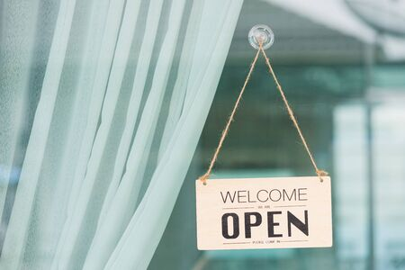 Close up of WELCOME WE ARE OPEN PLEASE COME IN notice sign wood board label hanging through glass door front shop, Business open back to new normal after coronavirus disease concept