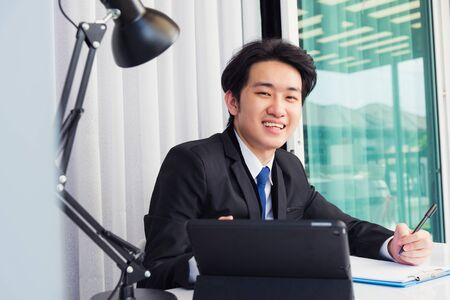 Work from home, Asian young businessman video conference call or facetime he smiling looking to camera sitting on desk using smart digital tablet computer and write notebook information at home office
