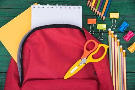 Top view Red bag backpack for education children on green wooden  background back to school concept Stok Fotoğraf