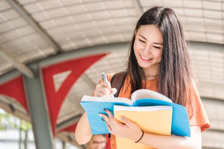 Young woman with backpack hold notebook standing in university Banque d'images