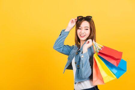 アジアの幸せな肖像画美しいかわいい若い女性の十代の笑顔サングラスで興奮した買い物袋を持ってマルチカラー見た目のバッグを隔離し、スタジオはコピースペースで黄色の背景を撮影しました