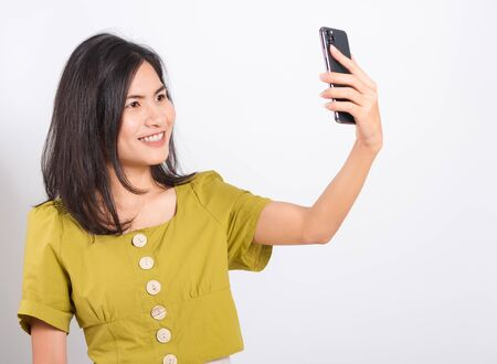 Portrait Asian beautiful happy young woman standing smile, holding mobile phone her taking selfie on white background, with copy space Imagens