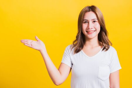 Asian Thai happy portrait beautiful cute young woman standing wear white t-shirt holding something on palm away side looking to camera, studio shot isolated on yellow background with copy space