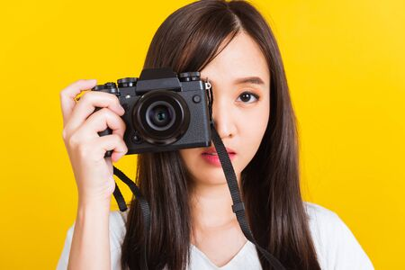 Portrait of happy Asian beautiful young woman photographer taking a picture and looking viewfinder on retro digital mirrorless photo camera ready to shoot, studio shot isolated on yellow background Banco de Imagens