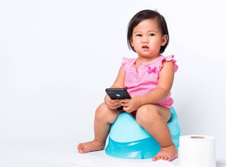 Asian little cute baby child girl education training to sitting on blue chamber pot or potty and play smart mobile phone with toilet paper rolls, studio shot isolated on white background, wc toilet