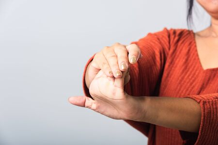 Close up hand of Asian woman she holding her acute pain in wrist of hands, studio shot isolated on white background, Healthcare medicine arthritis body care symptomatic office syndrome concept
