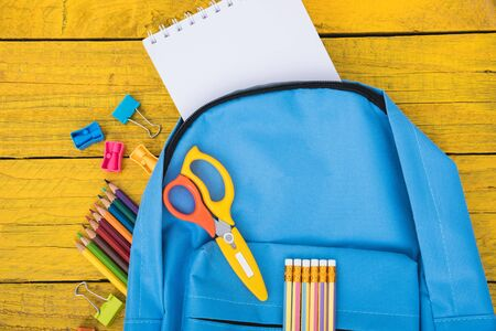 Top view flat lay of blue school bag backpack and accessories tools for children education on yellow wood background, Back to school concept and have copy space for use Stok Fotoğraf