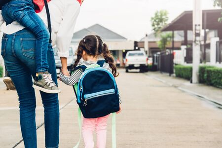 Happy Asian family children boy piggyback mother and walking sidewalk hold hand kid girl outdoors, the mother sends her child to school, Back to school first day of semester concept Stockfoto