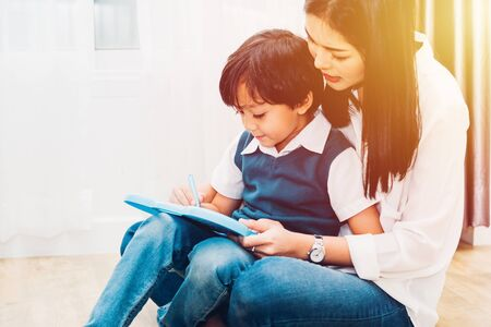 Happy Asian child kid boy son kindergarten and young beautiful parent mother teaching drawing and play color together at interior room home, family day and Back to school concept Standard-Bild