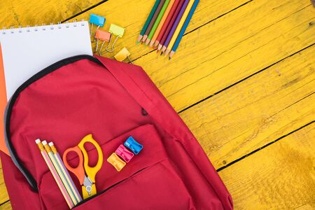 Top view flat lay of red school bag backpack and accessories tools for children education on yellow wood background, Back to school concept and have copy space for use