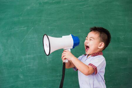 Back to School. Asian funny cute little child boy kindergarten preschool in student uniform speaking through megaphone against on green school blackboard, First time to school education concept Foto de archivo - 150373903