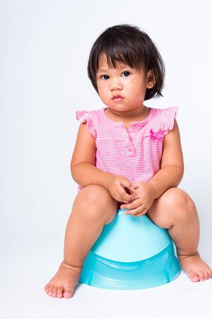 Asian little cute baby child girl education training to sitting on blue chamber pot or potty in, studio shot isolated on white background, wc toilet concept Stock Photo