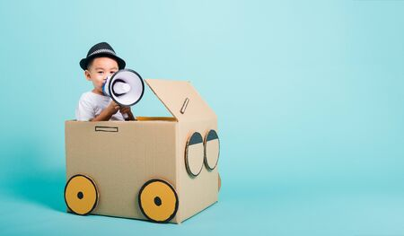 Happy Asian children boy smile in driving play car creative by a cardboard box imagination with megaphone, summer holiday travel concept, studio shot on blue background with copy space for text Foto de archivo - 150374083