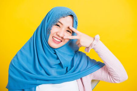 Asian Muslim Arab, Portrait of happy beautiful young woman Islam religious wear veil hijab smile she showing gesture hand two finger V-sign symbol near eyes isolated yellow background Foto de archivo
