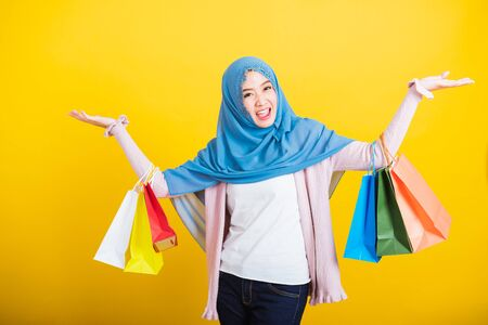 Asian Muslim Arab, Portrait of happy beautiful young woman Islam religious wear veil hijab funny smile she holding colorful shopping bags so glad shopping bags hand raise in studio isolated on yellow Foto de archivo
