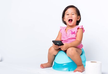 Asian little cute baby child girl education training to sitting on blue chamber pot or potty and play smart mobile phone with toilet paper rolls, studio shot isolated on white background, wc toilet Stock Photo