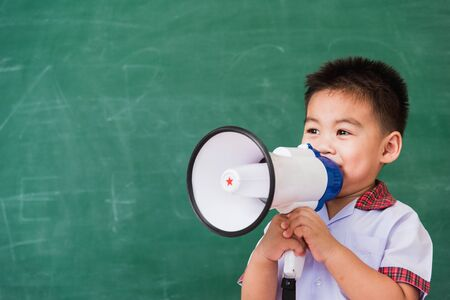 Back to School. Asian funny cute little child boy kindergarten preschool in student uniform speaking through megaphone against on green school blackboard, First time to school education concept