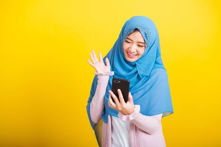 Asian Muslim Arab, Portrait of happy beautiful young woman Islam religious wear veil hijab funny smile she selfie or video call mobile smart phone raise hand say hello isolated on yellow background