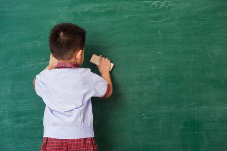 Back to School. Back of Asian cute little child boy kindergarten preschool in student uniform wiping clean or erase chalk on green school blackboard with sponge, First time to school education concept