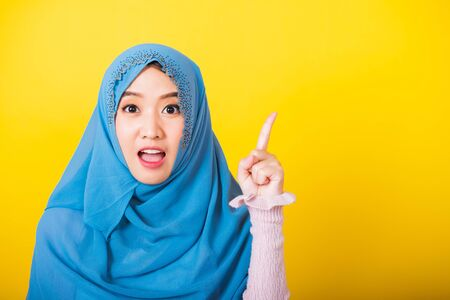 Asian Muslim Arab, Portrait of happy beautiful young woman Islam religious wear veil hijab funny smile she positive expression pointing with finger up to space isolated yellow background