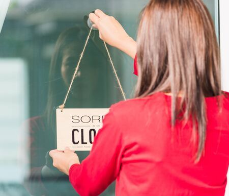 """Asian young woman notice sign wood board label """"SORRY WE ARE CLOSED PLEASE COME BACK AGAIN"""" hanging through glass door front shop, Business close during coronavirus pandemic disease concept"""