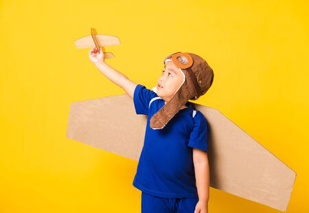 Happy Asian handsome funny child or kid little boy smile wear pilot hat play and goggles with toy cardboard airplane wings fly hold plane toy, studio shot isolated yellow background, Startup freedom Foto de archivo - 150374267