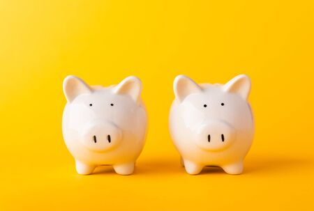 International Friendship Day, Front two small white fat piggy bank, studio shot isolated on yellow background and copy space for use, Finance, deposit saving money concept Stockfoto