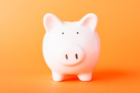 Front small white fat piggy bank, studio shot isolated on orange background and copy space for use, Finance, deposit saving money concept