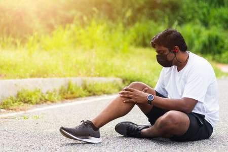 Close up Asian sport runner black man wear watch sitting he uses hands joint hold on his knee while running at the outdoor street health park, healthy exercise Injury from workout concept Banque d'images
