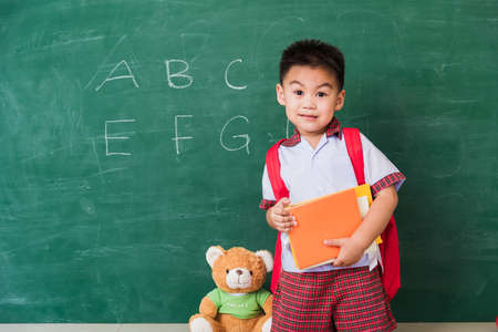 Back to School. Happy Asian funny cute little child boy from kindergarten in student uniform with school bag hold books smile on green school blackboard, First time to school education concept