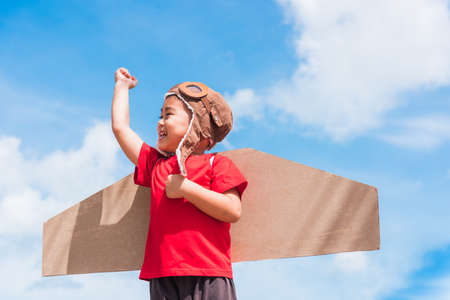 Happy Asian funny child or kid little boy smile wear pilot hat and goggles play toy cardboard airplane wing flying raises hand up against summer blue sky cloud background, Startup freedom concept