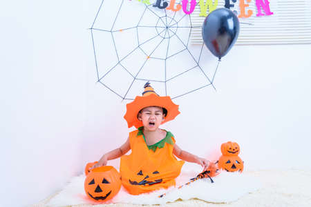 The little cute boy Kid on Halloween costume orange pumpkin he sitting in Halloween party house and open mouth for horror, Happy Halloween day concept Stock fotó