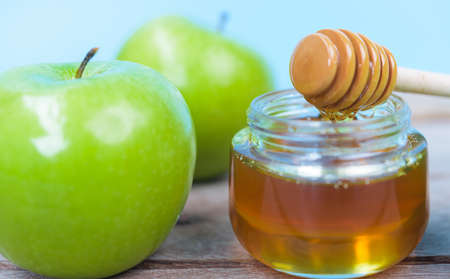 The Jewish holiday concept, Apples Rosh Hashanah day, on the photo have honey in jar and green apples on wooden with blue background