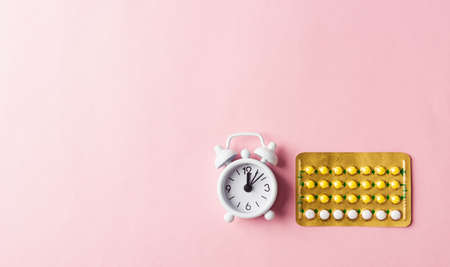World health or Aids day, Top view flat lay medicine birth control, alarm clock and contraceptive pills, studio shot isolated on a pink background, Safe and reproductive health concept