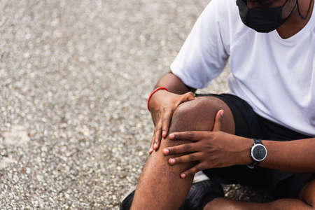 Close up Asian sport runner black man wear watch sitting he uses hands joint hold on his knee while running at the outdoor street health park, healthy exercise Injury from workout concept Banco de Imagens
