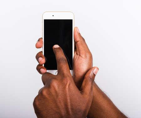 Closeup hand black man holding mockup white modern digital mobile smart phone blank screen on hand and point a finger to touch the screen, studio shot isolated on white background