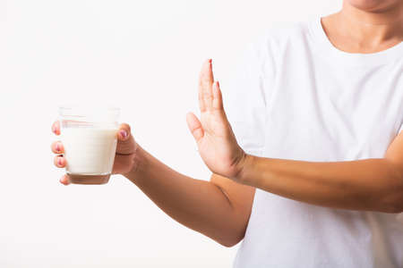 Closeup woman raises a hand to stop sign use hand holding glass milk she is bad stomach ache has bad lactose intolerance unhealthy problem with dairy food, studio shot isolated on white background